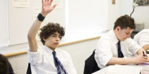 boy with raised hand in classromm