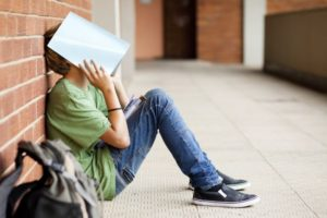 photo of boy with binder covering his face